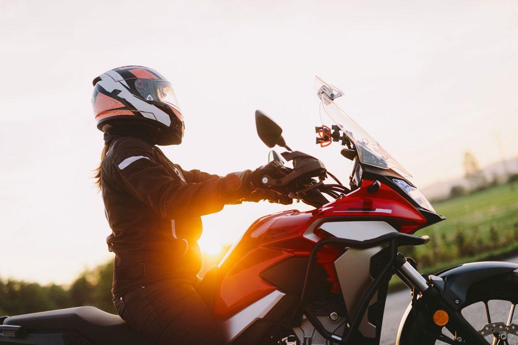Woman riding motorcycle at sunset