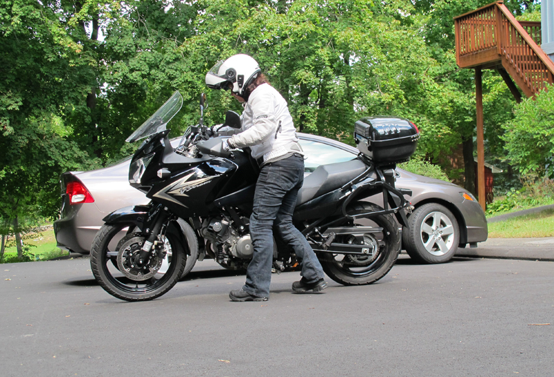 If both your feet can't touch the ground when seated on a motorcycle and you need to back out of (or into) a parking spot, walk the motorcycle by standing next to it. Grasp both grips from the left side of the bike as you upright it from its sidestand. Use your body as leverage and lean the motorcycle against your right hip, while backing it up in neutral or with the clutch squeezed. Cover the front brake while moving slowly. Again, practicing this maneuver on a small bike first is ideal, so you know how to do it with a bigger bike.