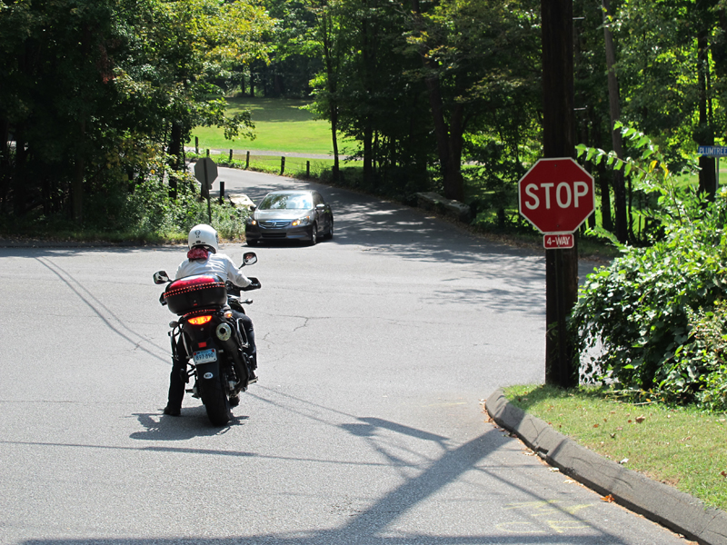 If you can reach the ground with tiptoes, you can then keep the front brake applied while you put your right foot down too. And always keep the handlebar squared off when you come to a stop, or else the motorcycle will want to fall in the direction they are turned.