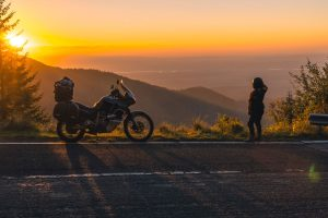 Biker stopped on roadside looking at sunset